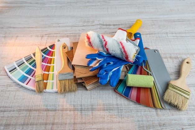 Zestaw rolek pędzli do malowania i palety kolorów papieru na desce. naprawa domu