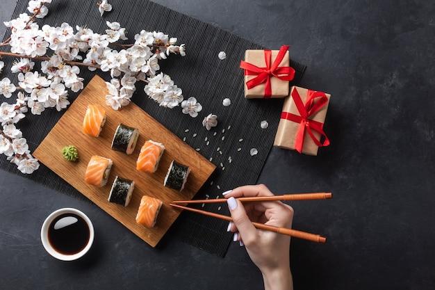 Zestaw rolek sushi i maki, ręka z pałeczkami, pudełka na prezenty i gałąź białych kwiatów na kamiennym stole. widok z góry.