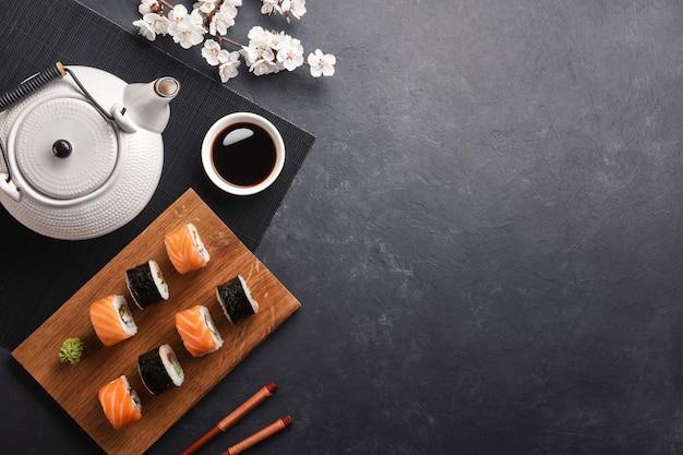 Zestaw rolek sushi i maki z czajniczek zielonej herbaty na kamiennym stole.