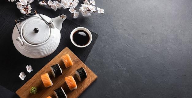 Zestaw rolek sushi i maki z gałązką białych kwiatów i czajniczek z napisem zielona herbata na kamiennym stole. widok z góry.