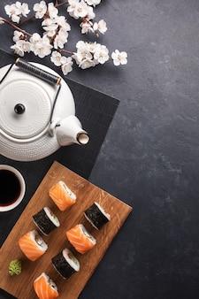 Zestaw rolek sushi i maki z gałęzi białych kwiatów i czajniczek z napisem zielona herbata na kamiennym stole. widok z góry.