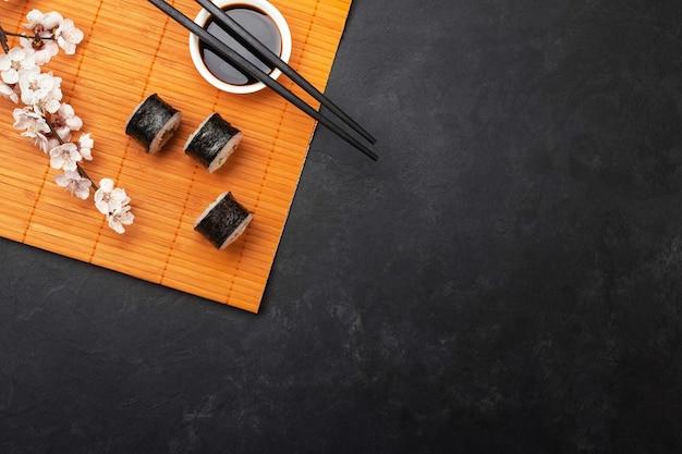 Zestaw rolek sushi i maki z gałęzi białych kwiatów na kamiennym stole. widok z góry.