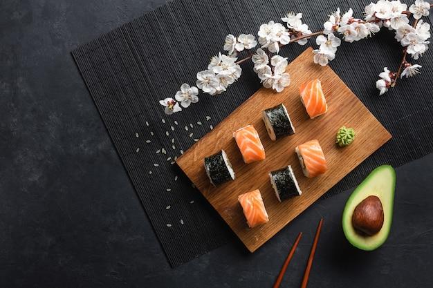 Zestaw rolek sushi i maki z pokrojonymi w plasterki awokado i gałązką białych kwiatów na kamiennym stole. widok z góry.
