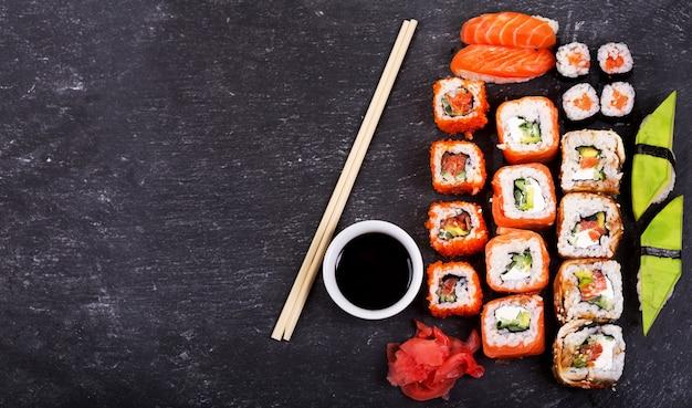 Zestaw rolek sushi i sashimi na ciemnym tle, widok z góry