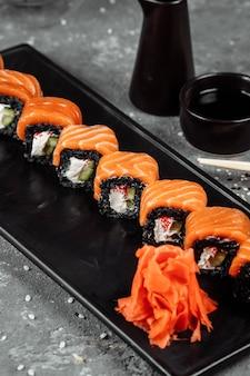 Zestaw rolek sushi philadelphia z czerwoną rybą, twarogiem i czarnym ryżem leży w łódce z talerza. rolki sushi na szarym tle.