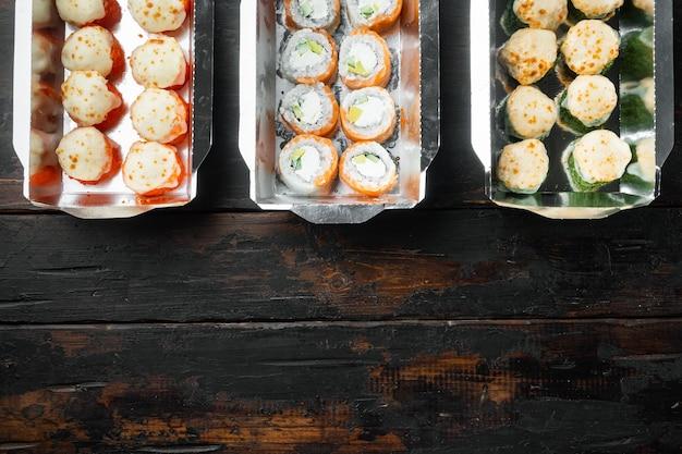 Zestaw rolek sushi w pudełku na dostawę żywności, na starym ciemnym drewnianym stole