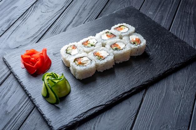 Zestaw rolek sushi z twarogiem, ryżem i łososiem na czarnej desce ozdobionej imbirem i wassabi na ciemnym drewnianym stole. kuchnia japońska. stolik ze zdjęciami żywności