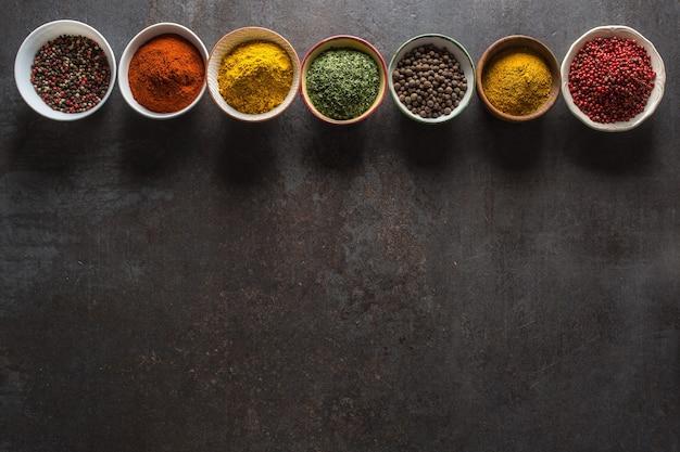 Zestaw różnorodnych aromatycznych przypraw i ziół w miseczkach.