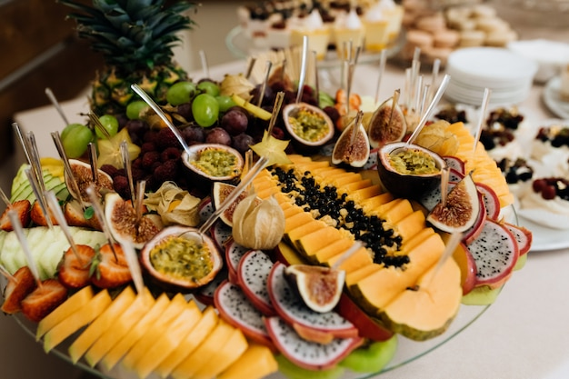 Zestaw różnorodnych egzotycznych owoców, krojonych na talerzu, bufet bankietowy
