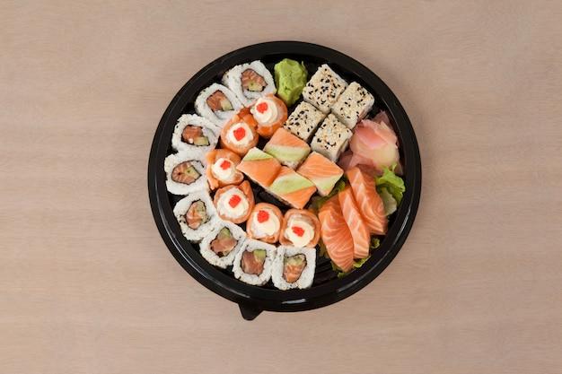 Zestaw różnorodnych sushi przechowywanych w czarnym okrągłym pudełku