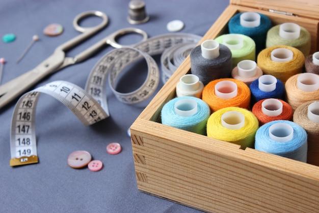 Zestaw różnych akcesoriów do szycia na kolorowym zbliżeniu tła