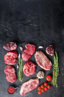 Zestaw różnych alternatywnych steków surowego mięsa na czarnym tle widok z góry. z miejscem na tekst.