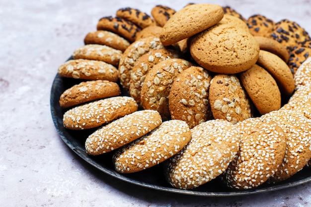 Zestaw różnych amerykańskich ciasteczek w stylu na jasnym tle betonu. kruche ciasteczka z konfetti, sezamem, masłem orzechowym, płatkami owsianymi i ciasteczkami czekoladowymi.