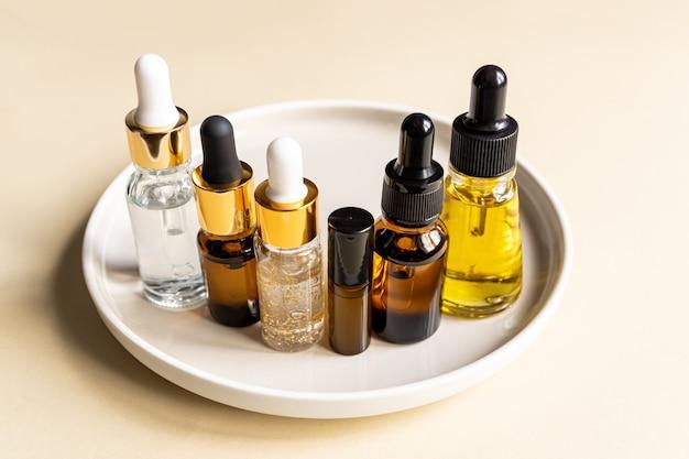 Zestaw różnych buteleczek z zakraplaczem z serum pielęgnacyjnym, kwasem hialuronowym i witaminami na ceramicznej tacy