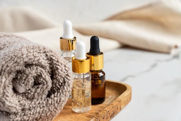 Zestaw różnych butelek z serum kosmetycznym, kwasem hialuronowym i witaminami na drewnianej tacy z ręcznikiem.