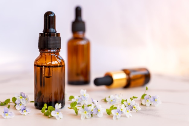 Zestaw różnych butelek z serum upiększającym, kwasem hialuronowym i witaminami na jasnej powierzchni z dzikimi kwiatami