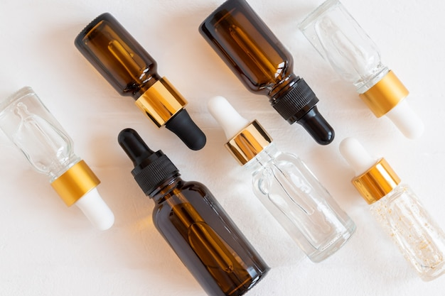 Zestaw różnych butelek z zakraplaczem z serum do pielęgnacji urody, kwasem hialuronowym i witaminami na drewnianym tle. kosmetyki domowe i koncepcja spa
