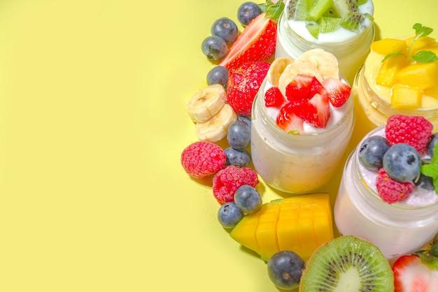 Zestaw różnych jogurtów owocowych i jagodowych w szklanych słoikach. odmiana zdrowego jogurtu śniadaniowego z jagodami, truskawkami, mango, kiwi, malinami, modnym jasnożółtym tłem z twardymi jasnymi ciemnymi cieniami