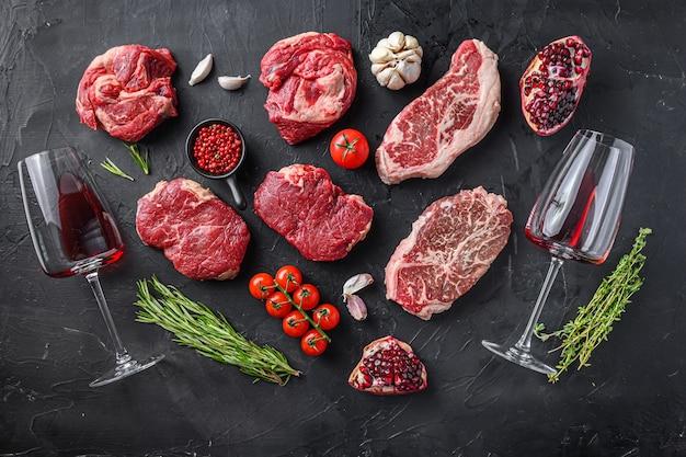 Zestaw różnych kawałków steków wołowych, roladki, rumsztyku i ostrza z ziołami, przyprawami i kieliszkiem do czerwonego wina na czarnym stole, widok z góry.