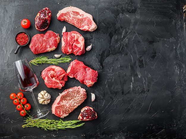 Zestaw różnych klasycznych, alternatywnych steków z surowego mięsa z kieliszkami czerwonego wina na czarnym tle widok z góry. duży rozmiar miejsca na tekst.