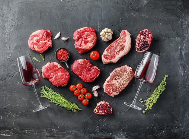 Zestaw różnych klasycznych, alternatywnych surowych steków mięsnych z kieliszkami czerwonego wina na czarnym tle widok z góry. duży rozmiar.