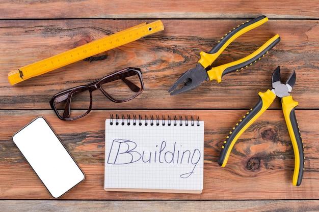 Zestaw różnych narzędzi budowlanych i smartfon na brązowym stole