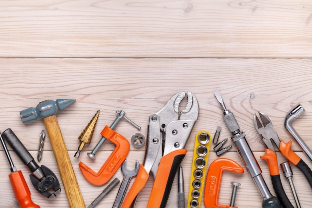 Zestaw różnych narzędzi domowych leżących w rzędzie na jasnym tle drewnianych. styl męski. strzał studio. skopiuj miejsce.
