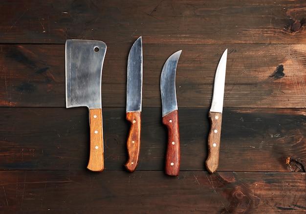 Zestaw różnych noży kuchennych z drewnianymi uchwytami na brązowym tle z desek