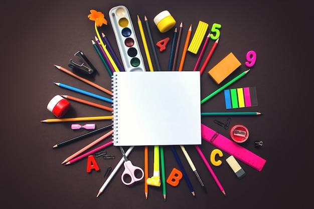 Zestaw różnych papeterii, budzik zeszyt szkolny i materiały eksploatacyjne na brązowym tle. powrót do koncepcji szkoły. format banera. widok z góry.