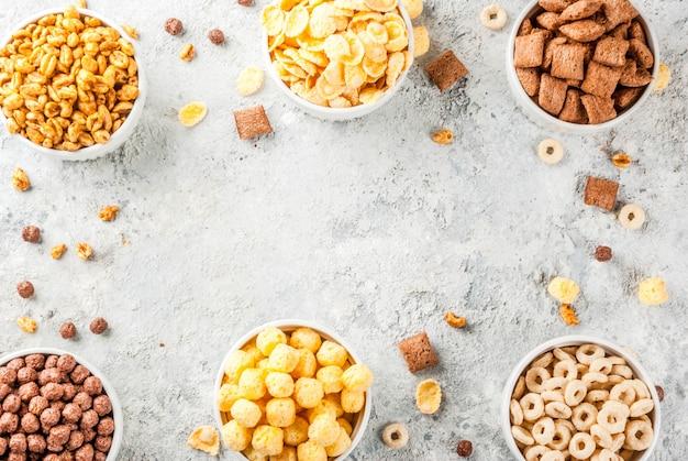 Zestaw różnych płatków kukurydzianych płatków śniadaniowych wyskakuje szara kamienna rama