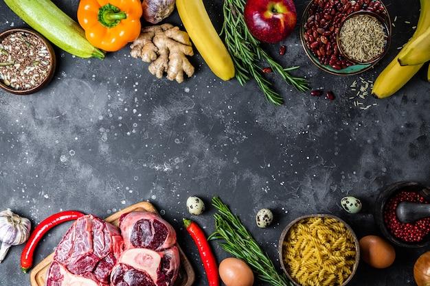 Zestaw różnych produktów do zdrowej diety - widok z góry mięsa, zbóż, warzyw i owoców, wybór między jedzeniem wegetariańskim i mięsnym, wolne miejsce na tekst. wysokiej jakości zdjęcie