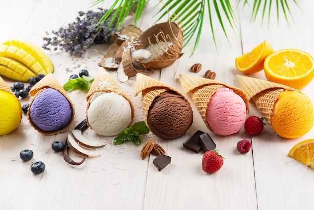 Zestaw różnych rodzajów lodów jagodowych i owocowych w rożkach waflowych