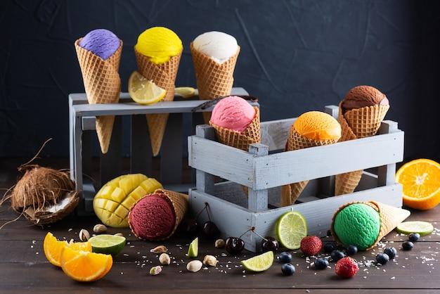 Zestaw różnych rodzajów lodów w drewnianych pudełkach na ciemnym tle