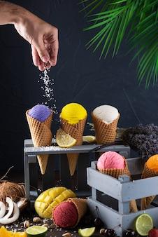 Zestaw różnych rodzajów lodów w rożkach waflowych z ręcznym posypywaniem płatków kokosowych