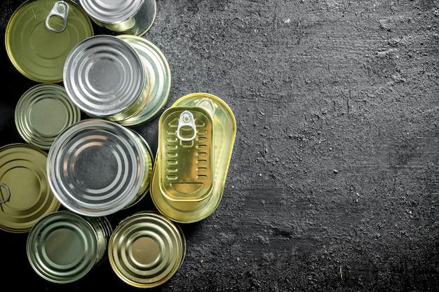 Zestaw różnych rodzajów puszek z konserwami. na czarnej powierzchni rustykalnej