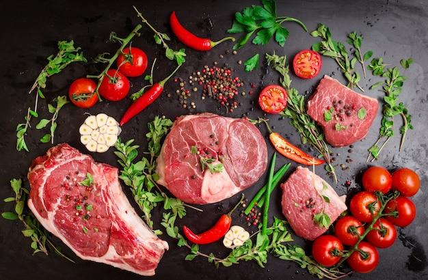 Zestaw różnych rodzajów steków. różne surowe mięso na tle czarnej kredy.