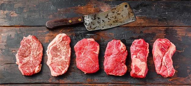 Zestaw różnych rodzajów surowych steków wołowych: górne ostrze, zad, chuck eye roll nad starym drewnianym tle widok z góry z tasakiem rzeźniczym.