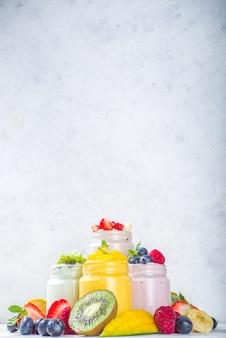 Zestaw różnych słodkich jogurtów owocowych i jagodowych w szklanych słoikach. odmiana zdrowy jogurt śniadaniowy z jagodami, truskawkami, mango, kiwi, malinami, ze świeżymi owocami i jagodami, białe drewniane tło