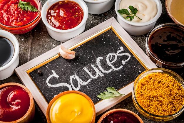 Zestaw różnych sosów: keczup, majonez, grill, soja, teriyaki, musztarda, zboża, pesto, adżika, chutney, tkemali, sos granatu na czarnym kamieniu. widok z góry