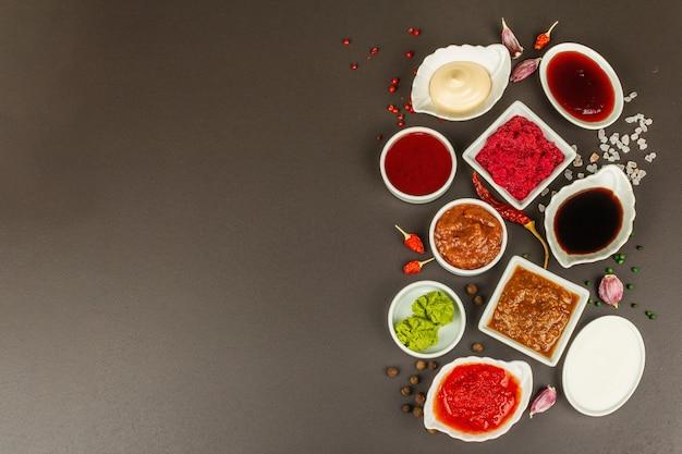 Zestaw różnych sosów - ketchup, majonez, barbecue, sojowy, chutney, wasabi, adjika, chrzanowy, aioli, marinara. ciemne kamienne tło betonowe, widok z góry