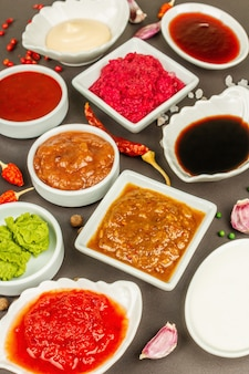 Zestaw różnych sosów - ketchup, majonez, barbecue, sojowy, chutney, wasabi, adjika, chrzanowy, aioli, marinara. ciemne kamienne tło betonowe, z bliska