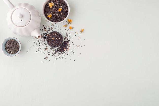 Zestaw różnych suchych herbatek ziołowych i owocowych na lekkim stole.