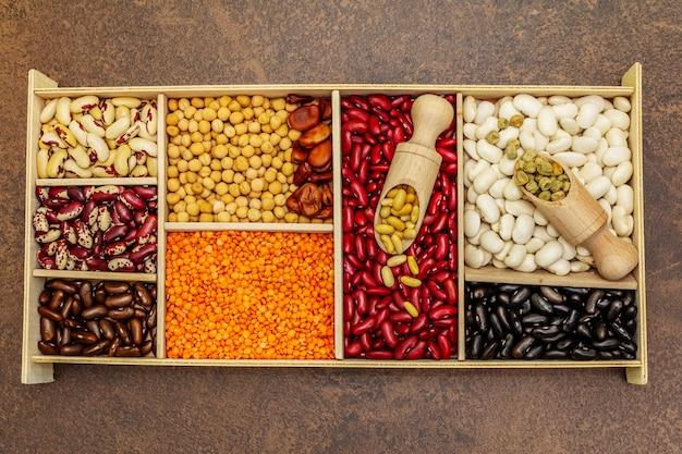 Zestaw różnych suchych roślin strączkowych w drewnianym pudełku