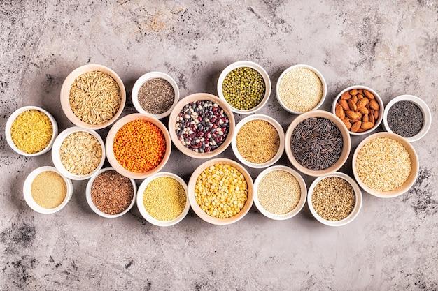 Zestaw różnych superfoods - produkty pełnoziarniste, fasola i rośliny strączkowe, nasiona i orzechy, widok z góry.