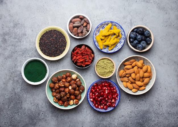 Zestaw różnych superfoods w miskach na kamiennym szarym tle: spirulina, jagody goji, kakao, proszek zielonej herbaty matcha, quinoa, nasiona chia, jagody, orzechy dla szczęśliwego zdrowego trybu życia, widok z góry, zbliżenie