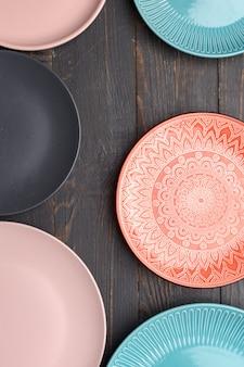 Zestaw różnych talerzy na ciemnym drewnianym stole. widok z góry.