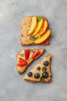 Zestaw różnych tostów z masłem orzechowym; kochanie; mennica; orzeszki ziemne, nektarynka, jagoda i truskawka