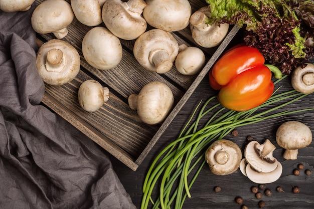 Zestaw różnych warzyw i pieczarek w drewnianym pudełku. ciemny drewniany stół.