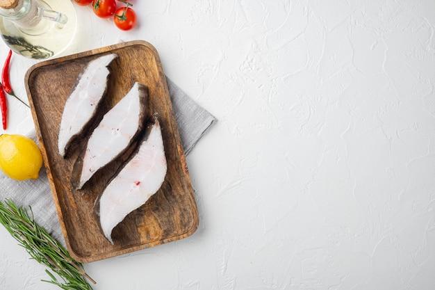 Zestaw ryb halibuta w plasterkach, ze składnikami i ziołami rozmarynu, na białym tle kamiennego stołu, widok z góry płaski, z miejscem na kopię dla tekstu