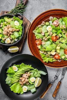 Zestaw sałatek z awokado, krewetkami, krewetkami i zieleniną w miseczkach.